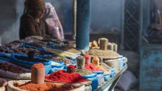 Photo of a woman selling what looks like spices